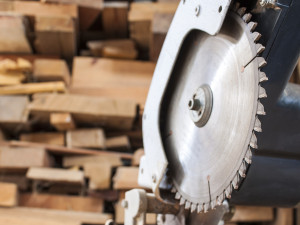 Compound Mitre Saw cutting planks wooden background